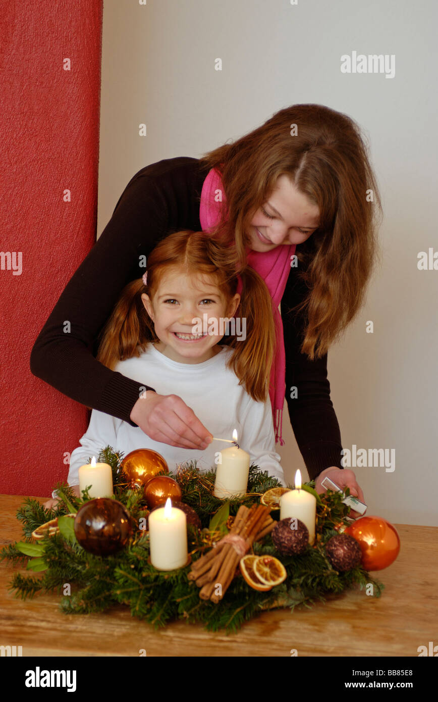 Young woman and her daughter are lighting candles on an advent wreath - Stock Image