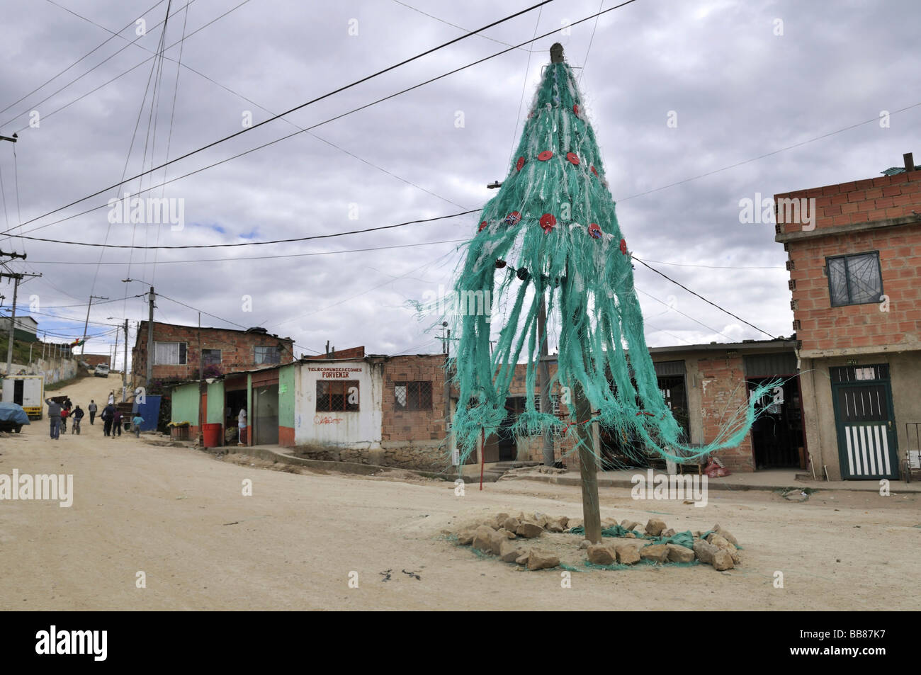 Huge aging Christmas tree blowing in the wind on a town square, slums of Alto de Cazuca, Soacha, Bogotá, Columbia - Stock Image