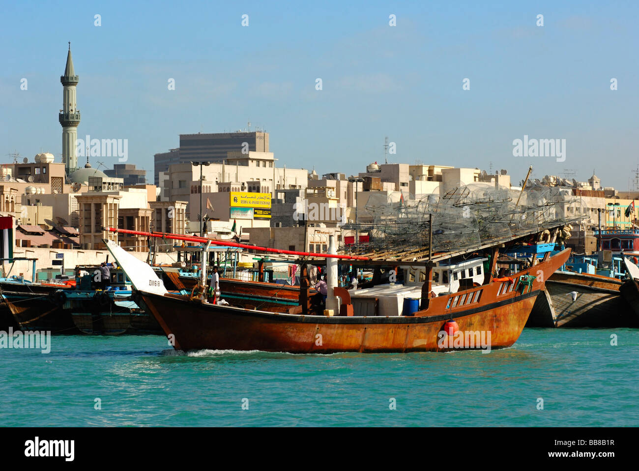 A traditional fisher boat heading out to fish loaded with bow nets in the Dubai Creek in front of the back-drop - Stock Image