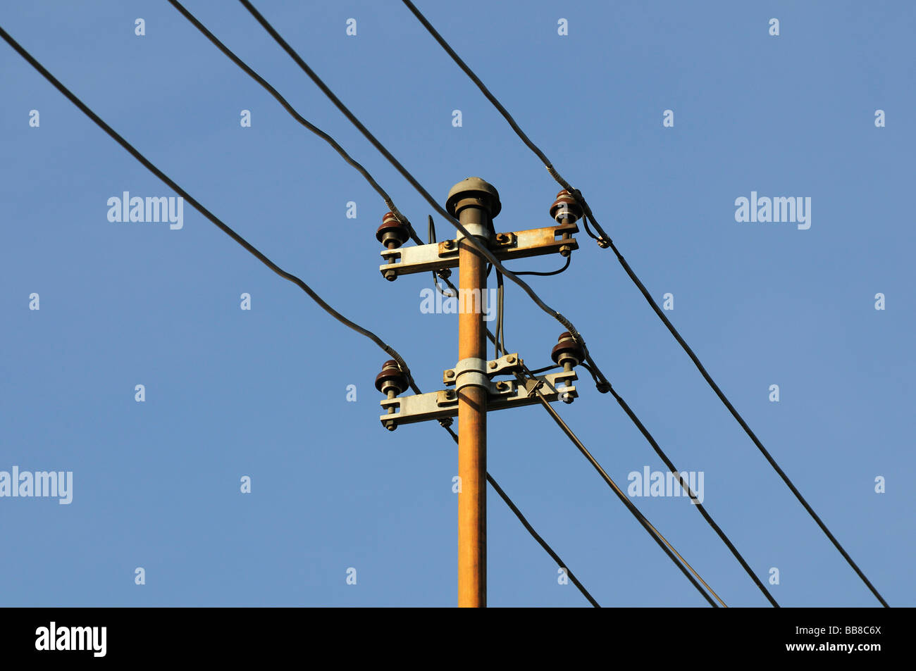 View of an old house utility pole with 4 wires and ceramic insulators in front of a blue sky, power supply - Stock Image