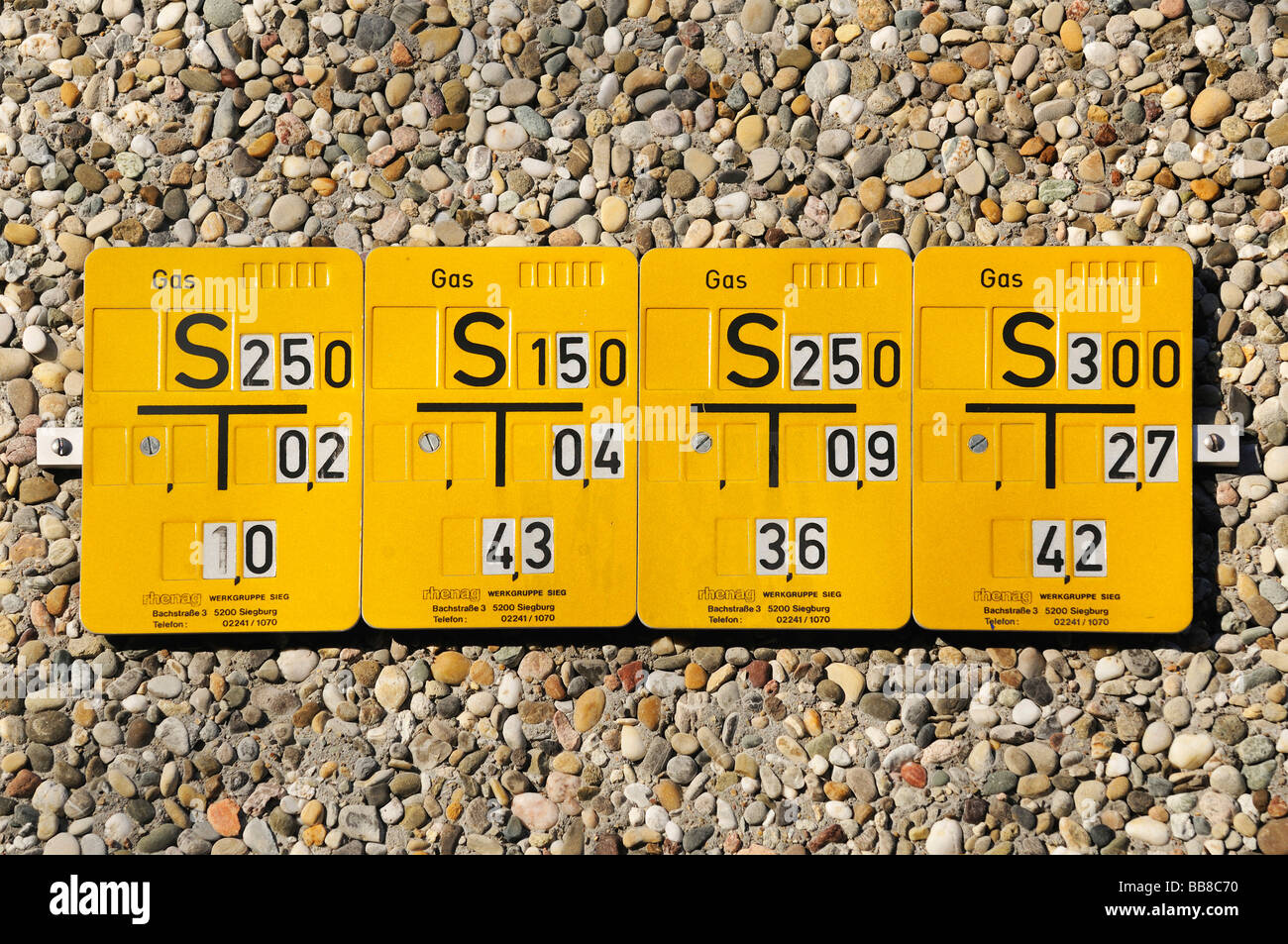 4 indicating panels for gas lines next to each other on a pebble wall, Rhenag - Stock Image