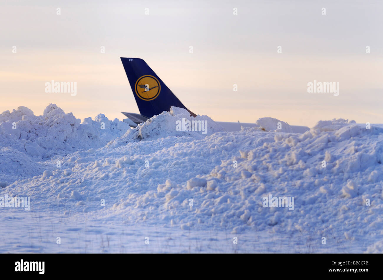 Lufthansa tail fin behind snow mounds beside a runway - Stock Image