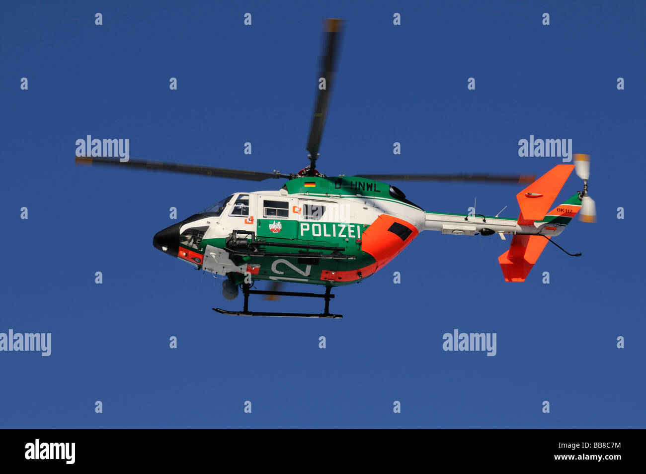 Police helicopter in flight against a steel-blue sky - Stock Image