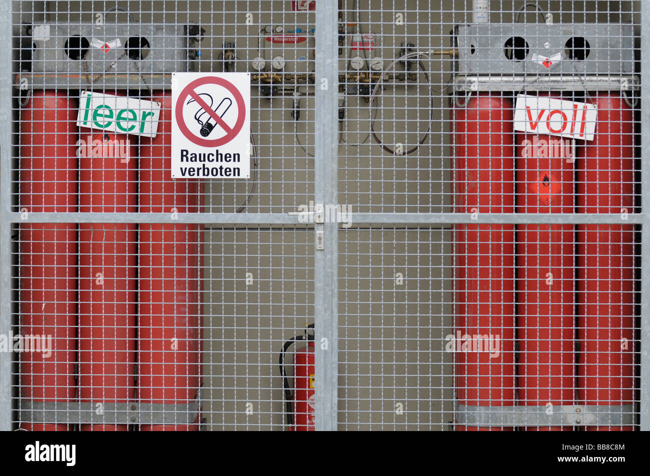 Hydrogen refilling station, empty and full red gas bottles behind a protective wire grid, fittings and gauges, prohibition - Stock Image