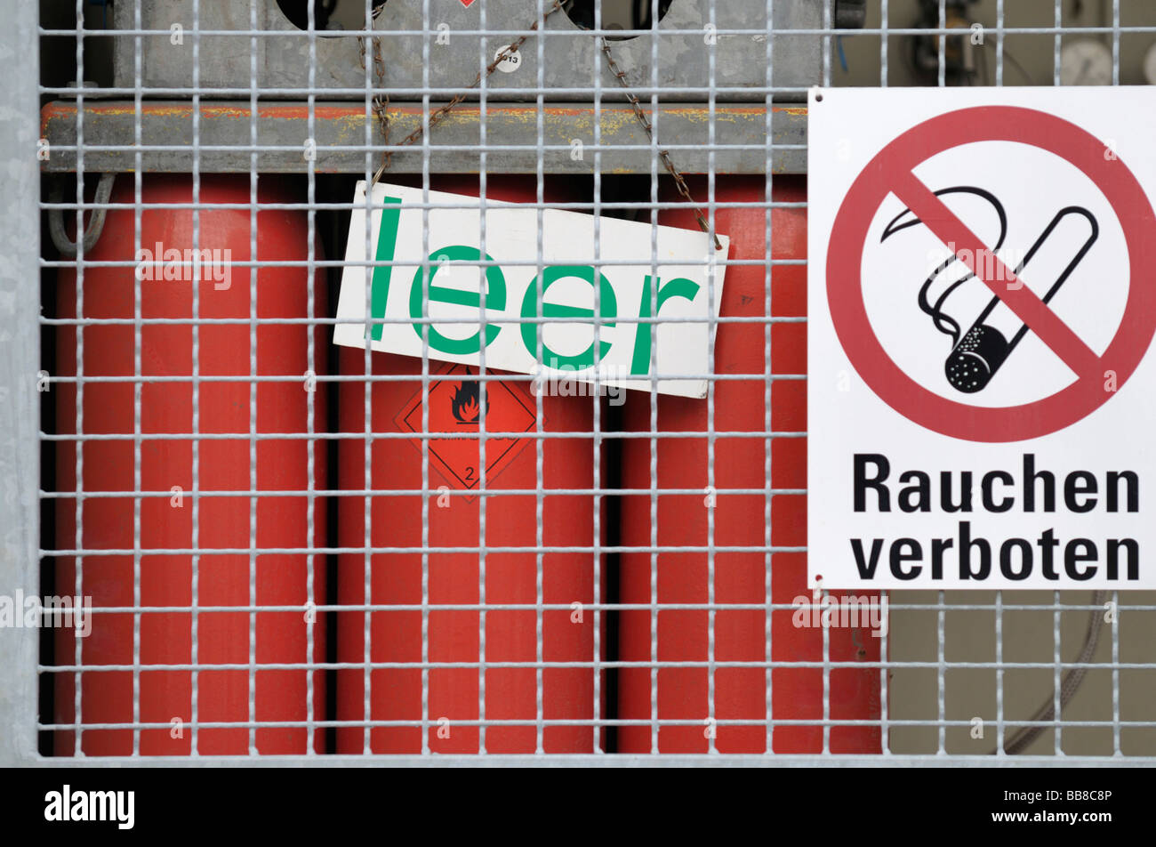 Empty red gas bottles behind a protective wire grid, prohibition sign, smoking forbidden - Stock Image