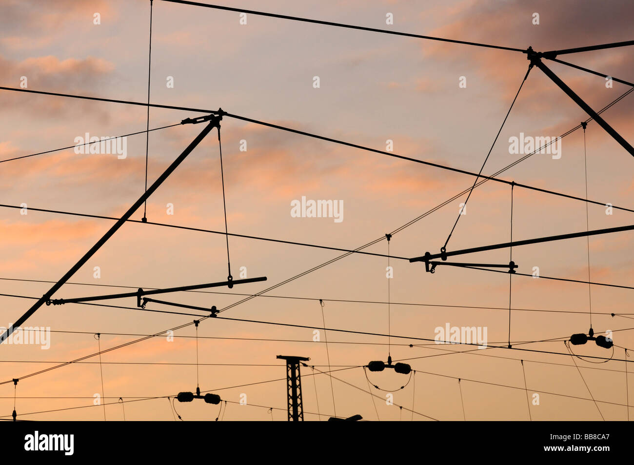 Commuter railway system and German Federal Railways catenary in sunset light Stock Photo