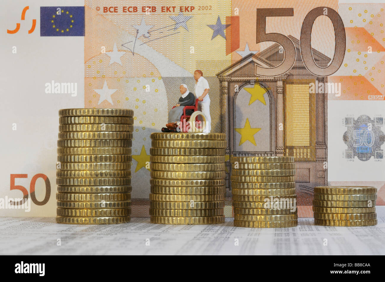 Stacked coins, 50 euro banknotes at back, attendant pushing senior citizen in wheelchair, figures, symbolic of increase - Stock Image