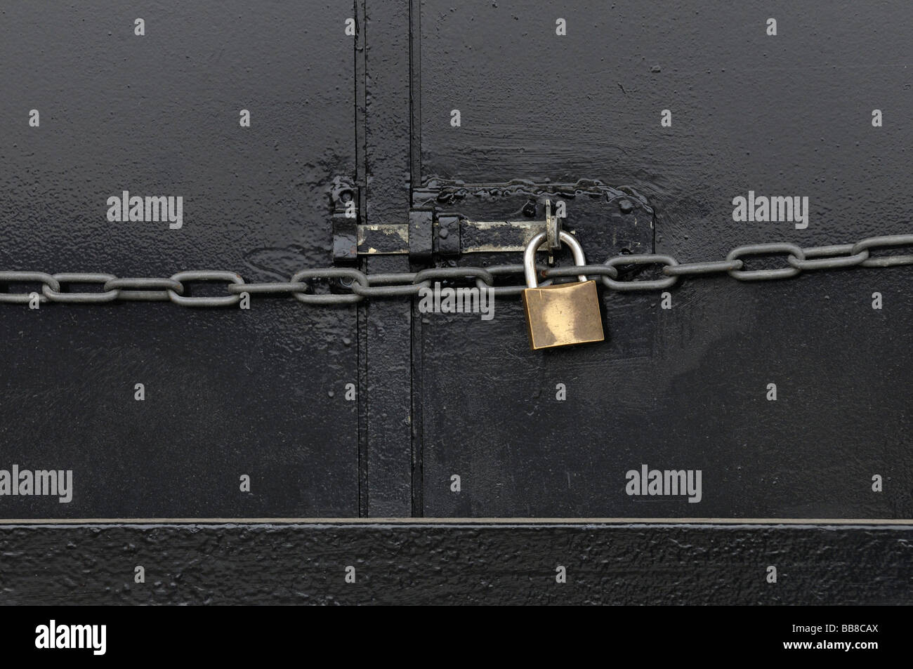 Metal door secured by bar with padlock and chain - Stock Image