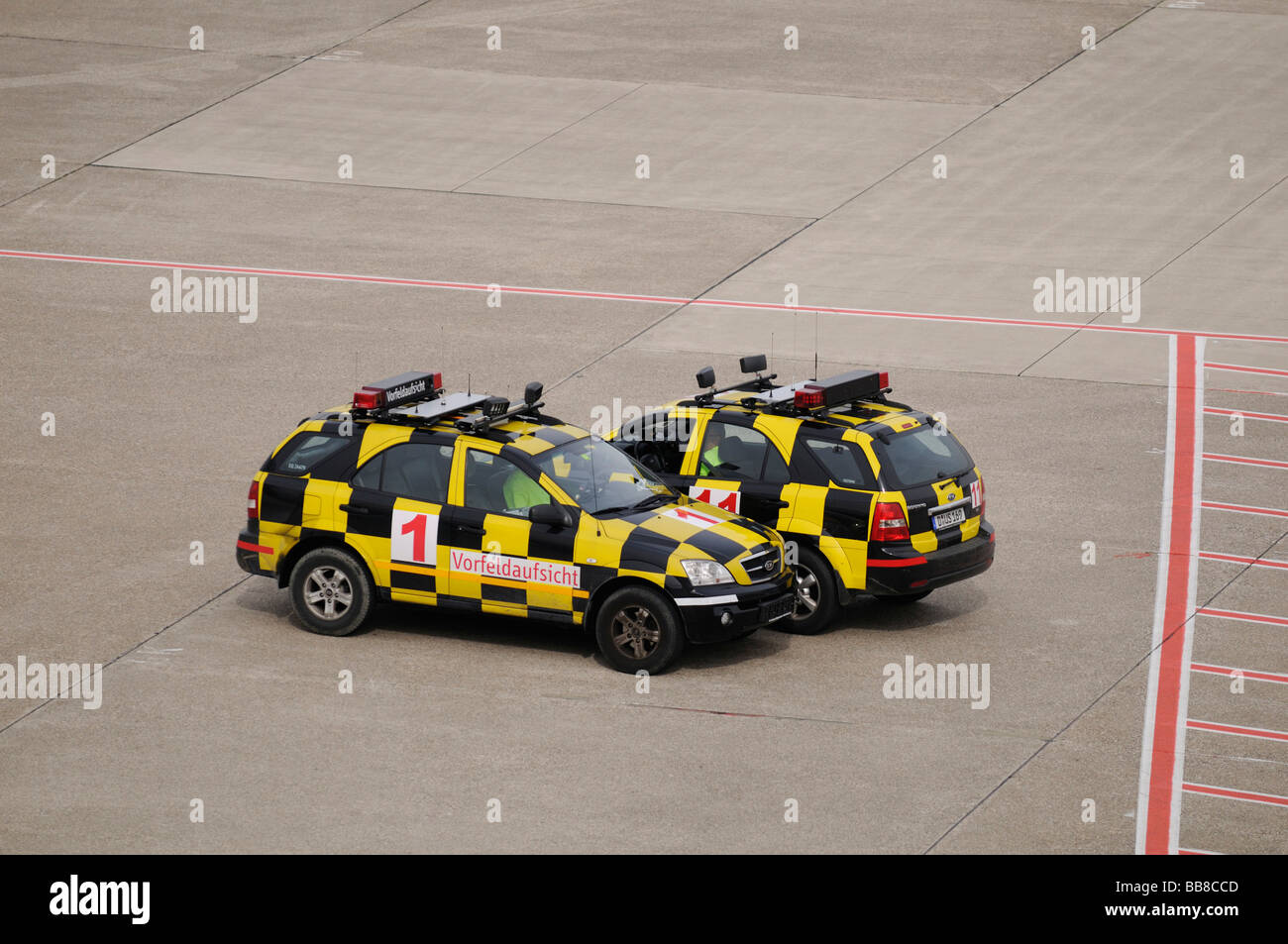 Two yellow and black chequered vehicles on a runway, follow-me cars, Duesseldorf International Airport, North Rhine - Stock Image