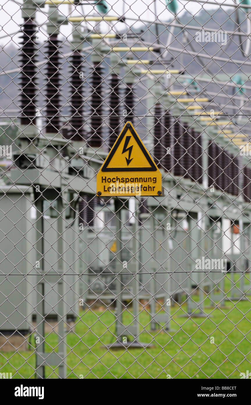 Sign, high voltage, risk of fatal injury, on a wire mesh fence, in front of an electrical transformer station Stock Photo