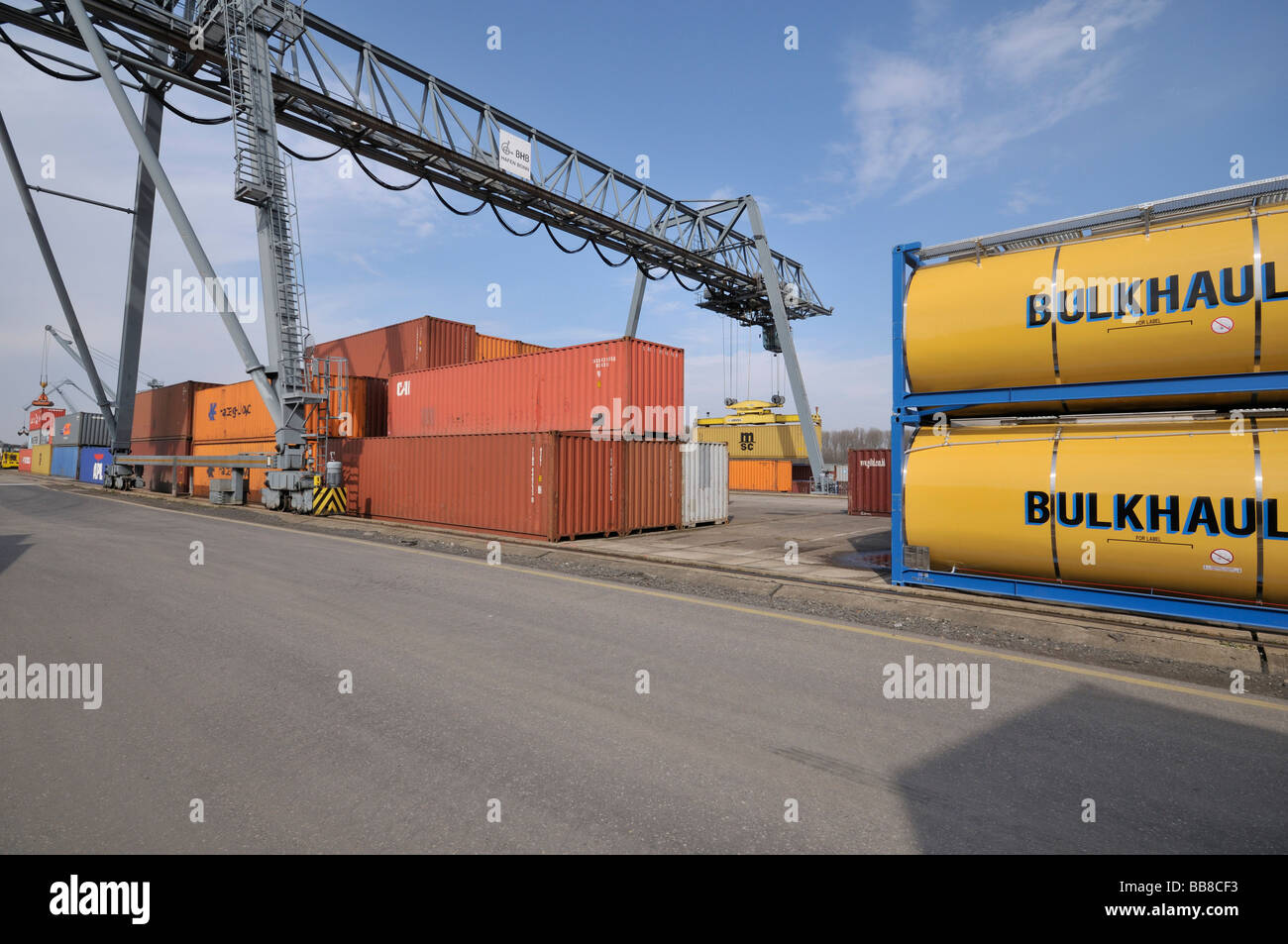 Container terminal Bonn, tank containers and Iso containers, next to it gantry crane lifting container on deck of - Stock Image