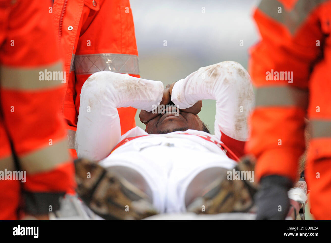 Arthur Boka, football player, VfB Stuttgart, being carried from the field on a stretcher by paramedics - Stock Image