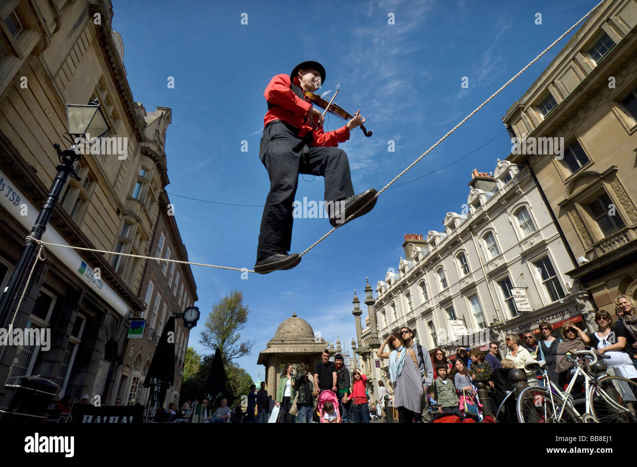 A Street Theatre busker plays a violin while balancing  on a tightrope during Brighton Festival - Stock Image