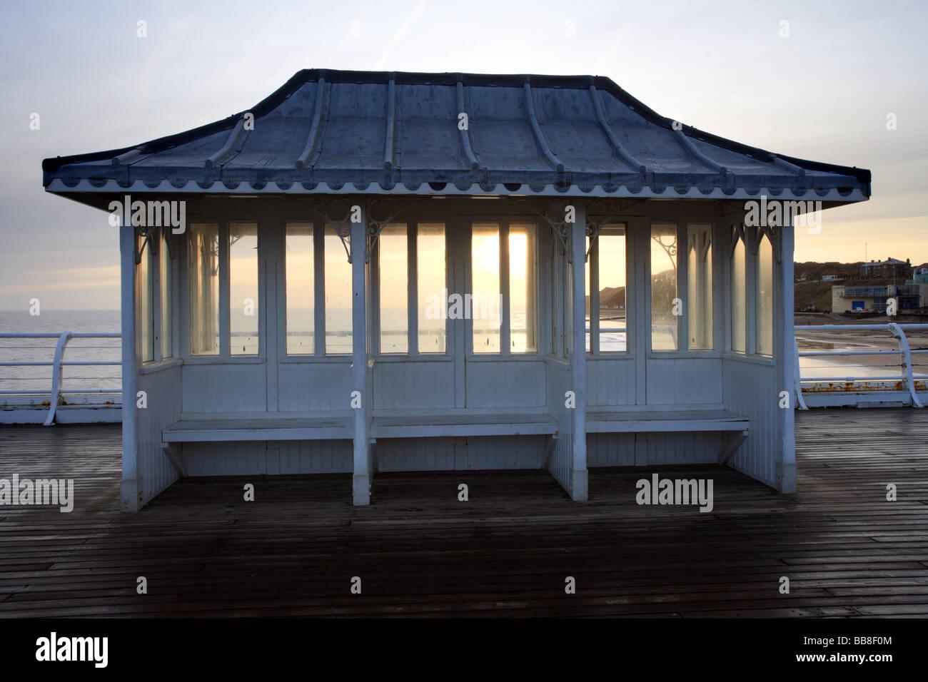 Rain Shelter, 'Seaside shelter' on Cromer Pier, Norfolk, UK sunrise over the sea. - Stock Image