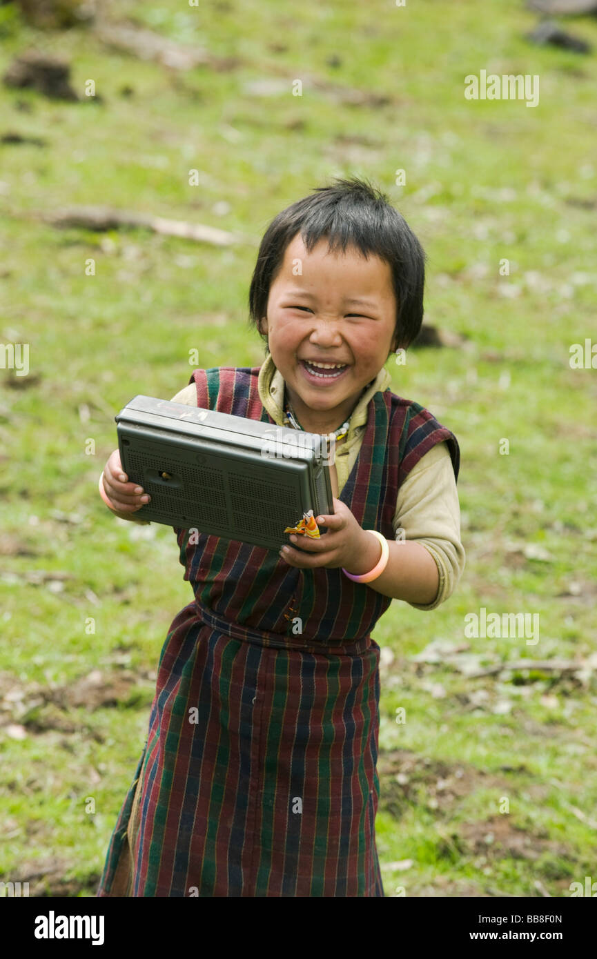 Young girl, Yak-herding family. enjoys radio. Pele La Pass. ca. 11,000 feet, BHUTAN - Stock Image