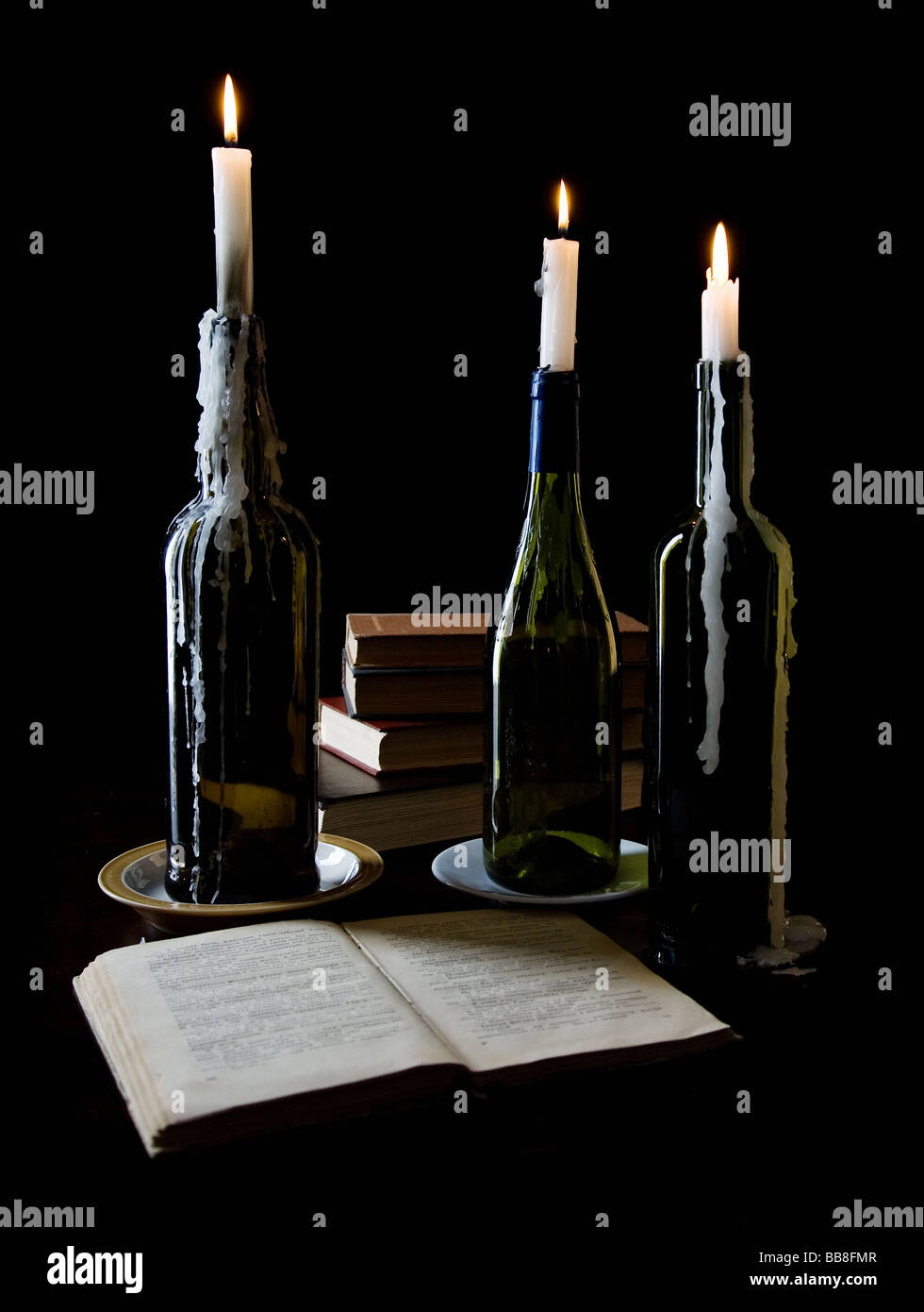 Three candles and books on black background - Stock Image