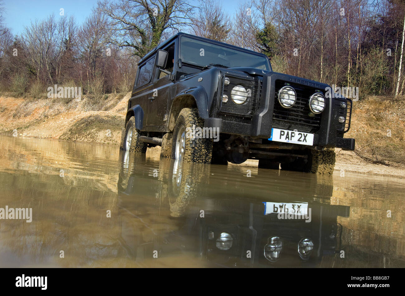 A Landrover Defender driving through a flood on an off road exercise - Stock Image