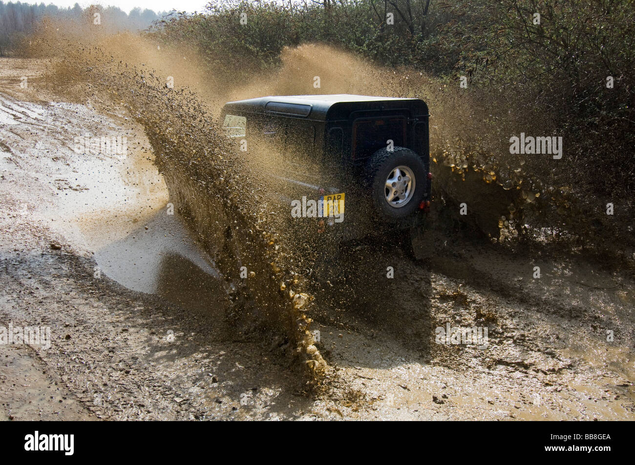 A Landrover Defender driving along a muddy track on an off road exercise - Stock Image