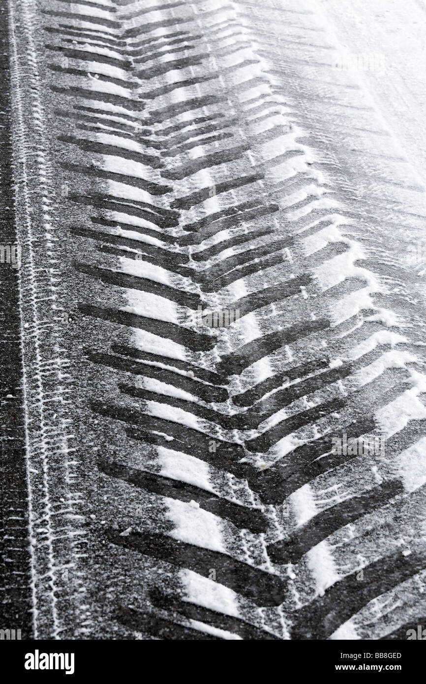 Tyre tracks of a tractor on a snowy and icy road - Stock Image