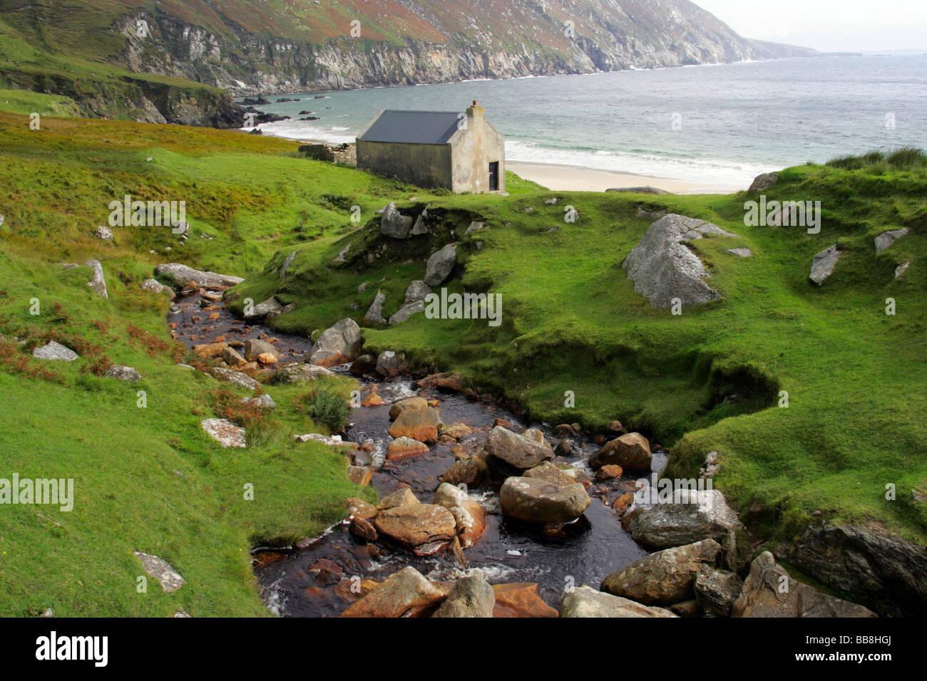 Stone cottage on coast near Keel, Achill Island, County Mayo, Ireland - Stock Image