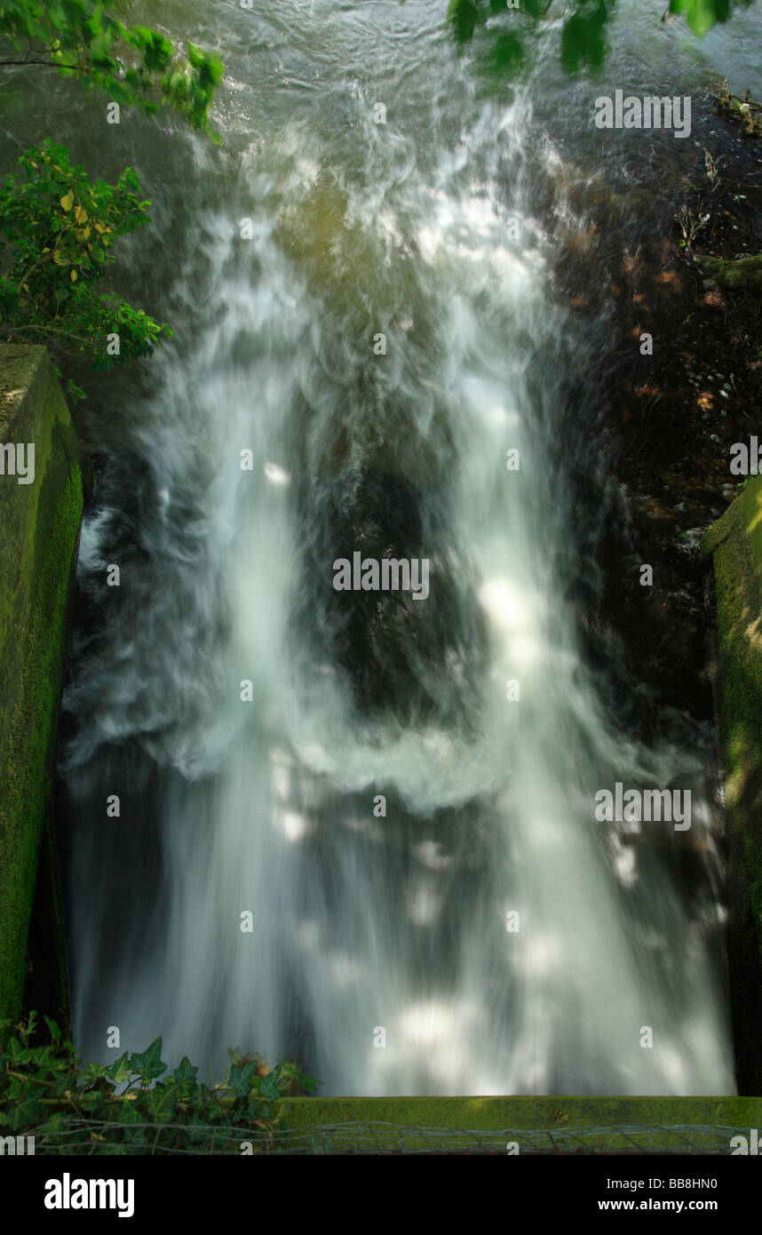 White water from above a mill sluice flowing out. - Stock Image