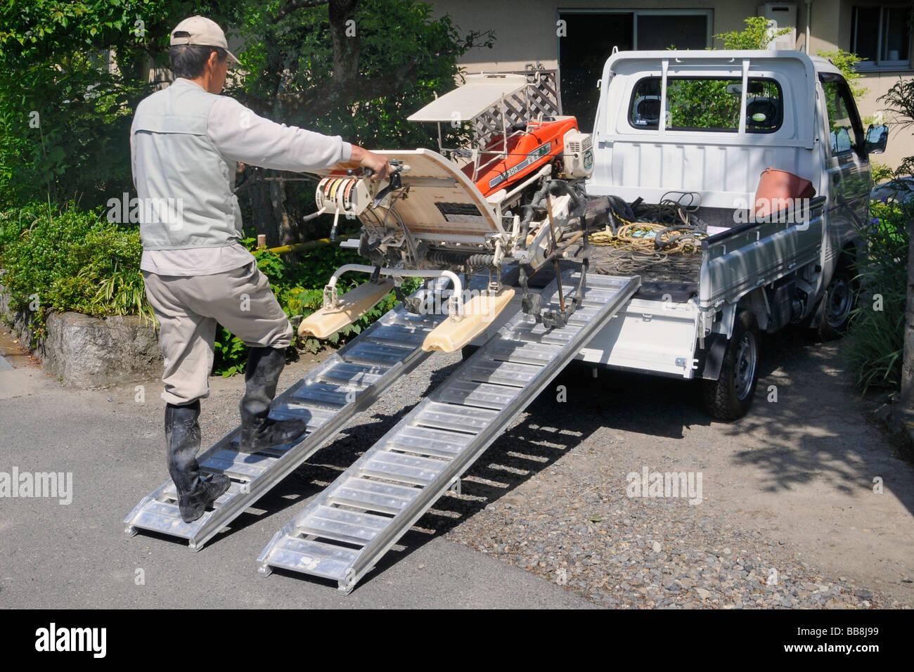 Rice farmer loading his rice-planting machine on to his small truck, Iwakura, Kyoto, Japan, Asia - Stock Image