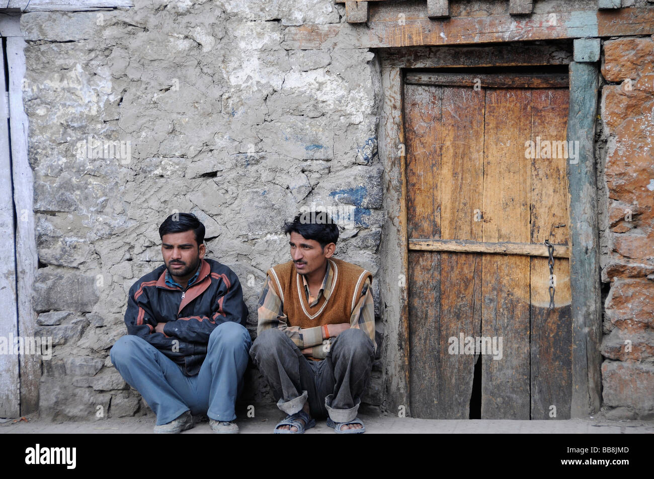 Squatting Hindi men, immigrant workers in front of their house in Leh, Ladakh, North India, Himalayas, Asia - Stock Image