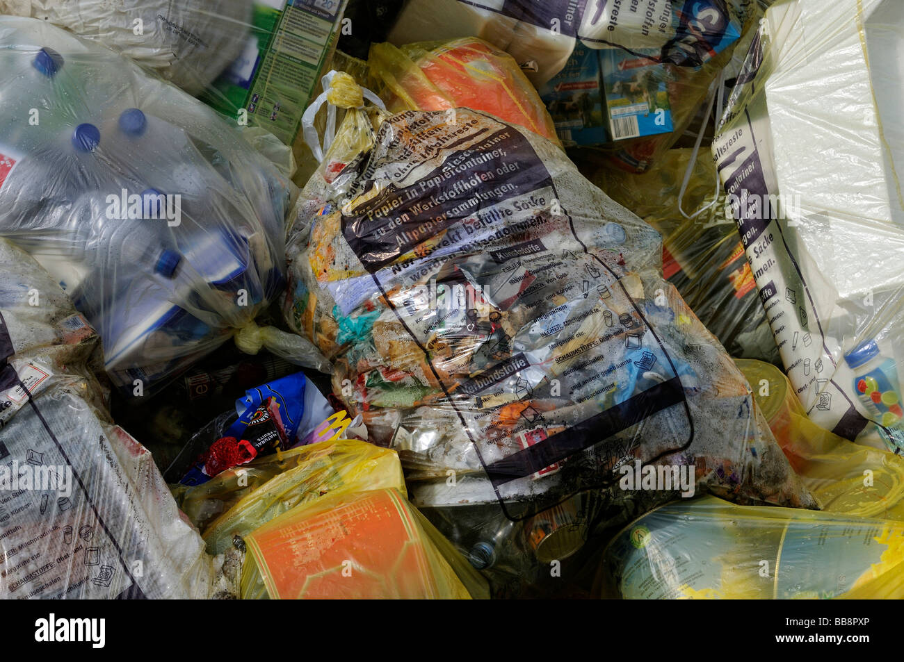 Garbage filled yellow sacks to be recycled - Stock Image