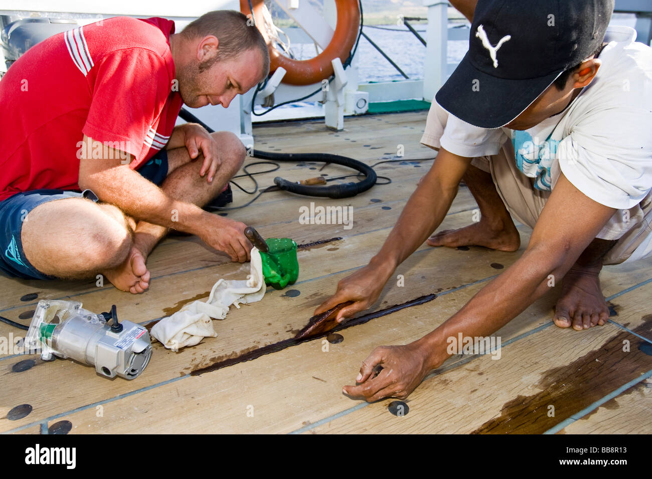Sailors sealing planks on a ship, Indonesia - Stock Image