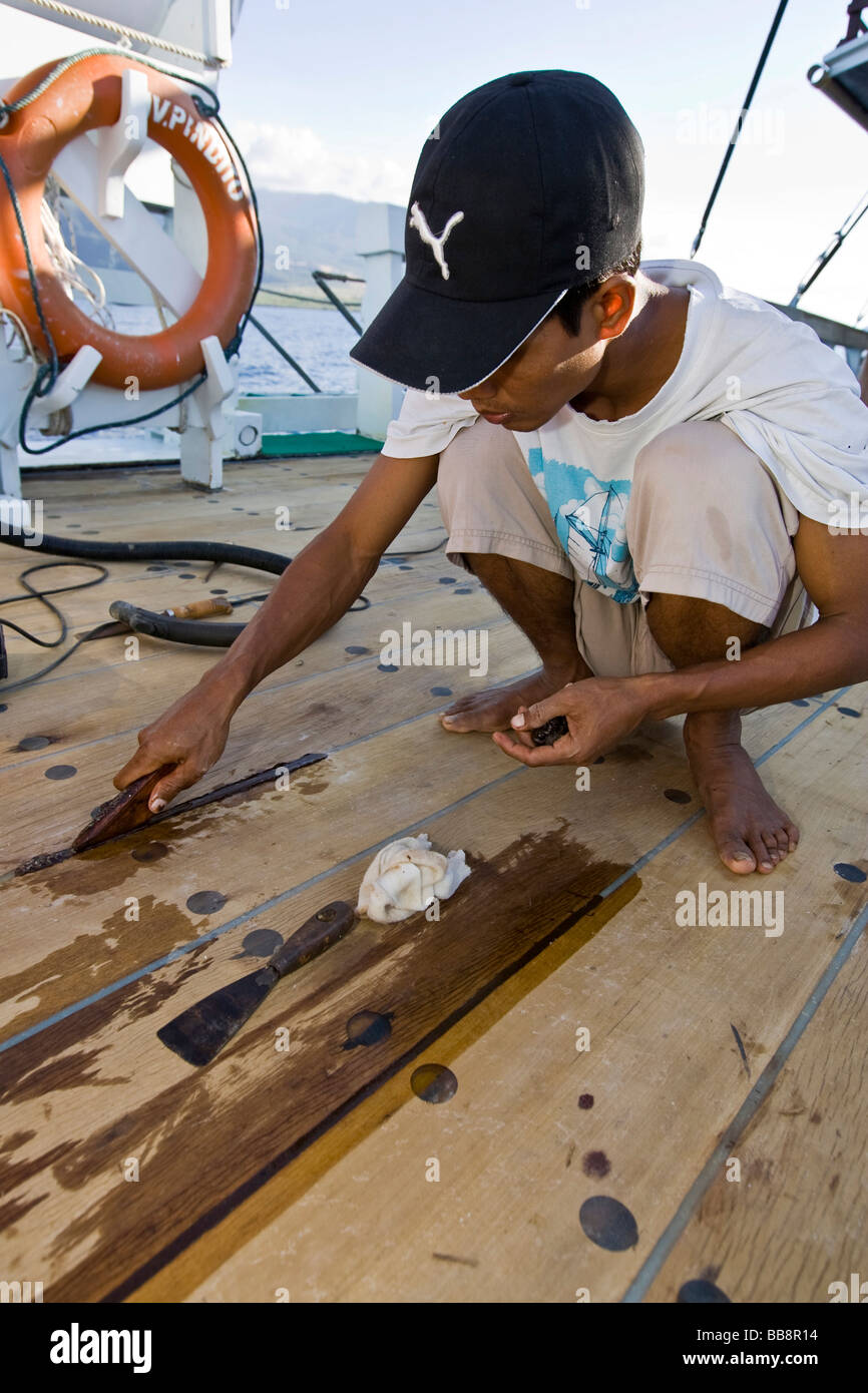 Sailor sealing planks on a ship, Indonesia - Stock Image