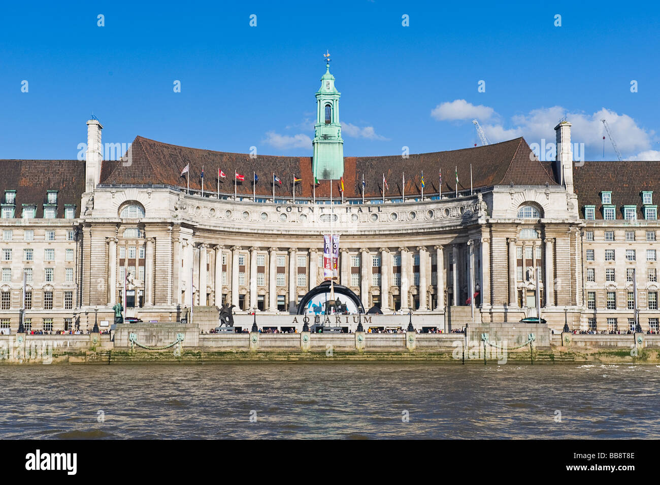 The old County Hall , was seat of GLC , now site of London Aquarium & hotel , seen from River Thames on bright - Stock Image