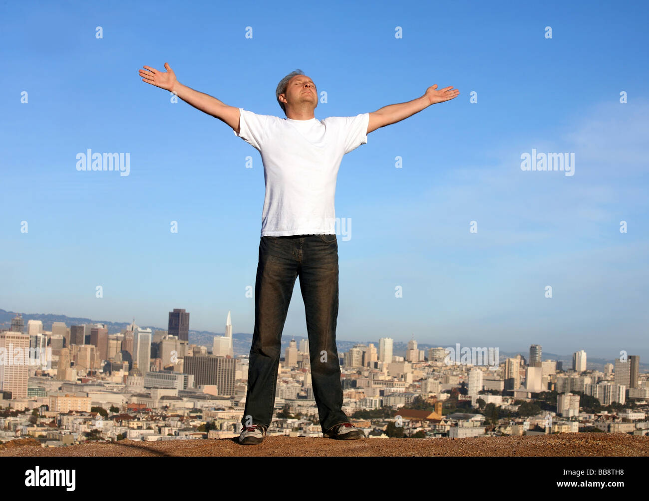 A man standing on a hill with a view of San Francisco his arms raised - Stock Image