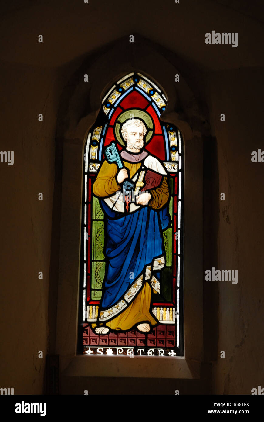 Stained glass window with a depiction of St Peter St Peter s Church in Old Woking Surrey England The church is a - Stock Image