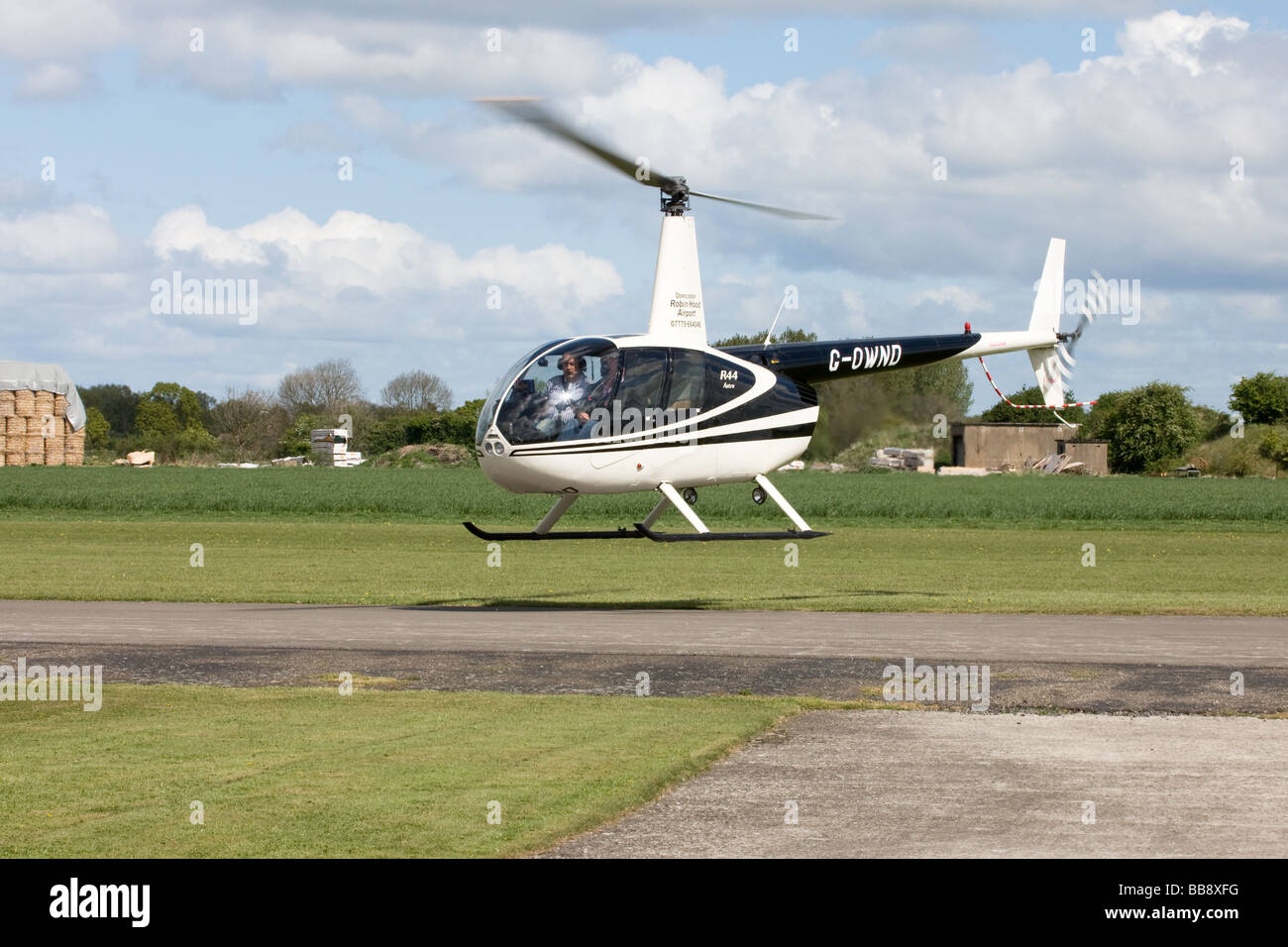 Robinson R44 Astro G-OWND hovering ready to depart at Breighton Airfield - Stock Image