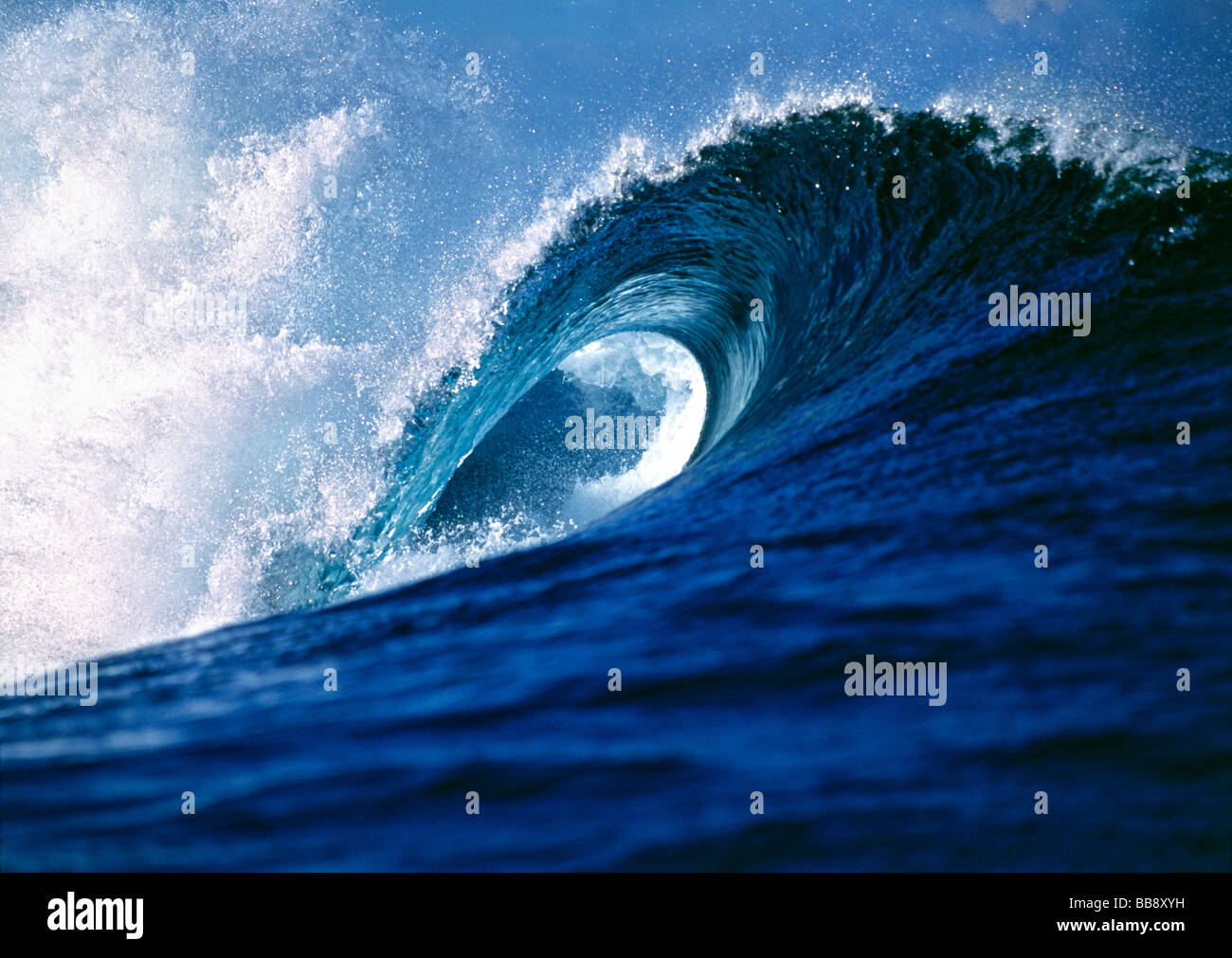 A wave creates a perfect curl at Cloudbreak near Tavarua Fiji Islands - Stock Image