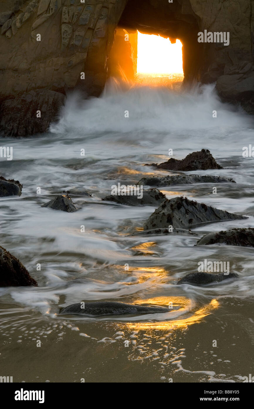 The sun sets through a window to the Pacific - Pfeiffer State Beach, Big Sur Coast, California, USA. - Stock Image
