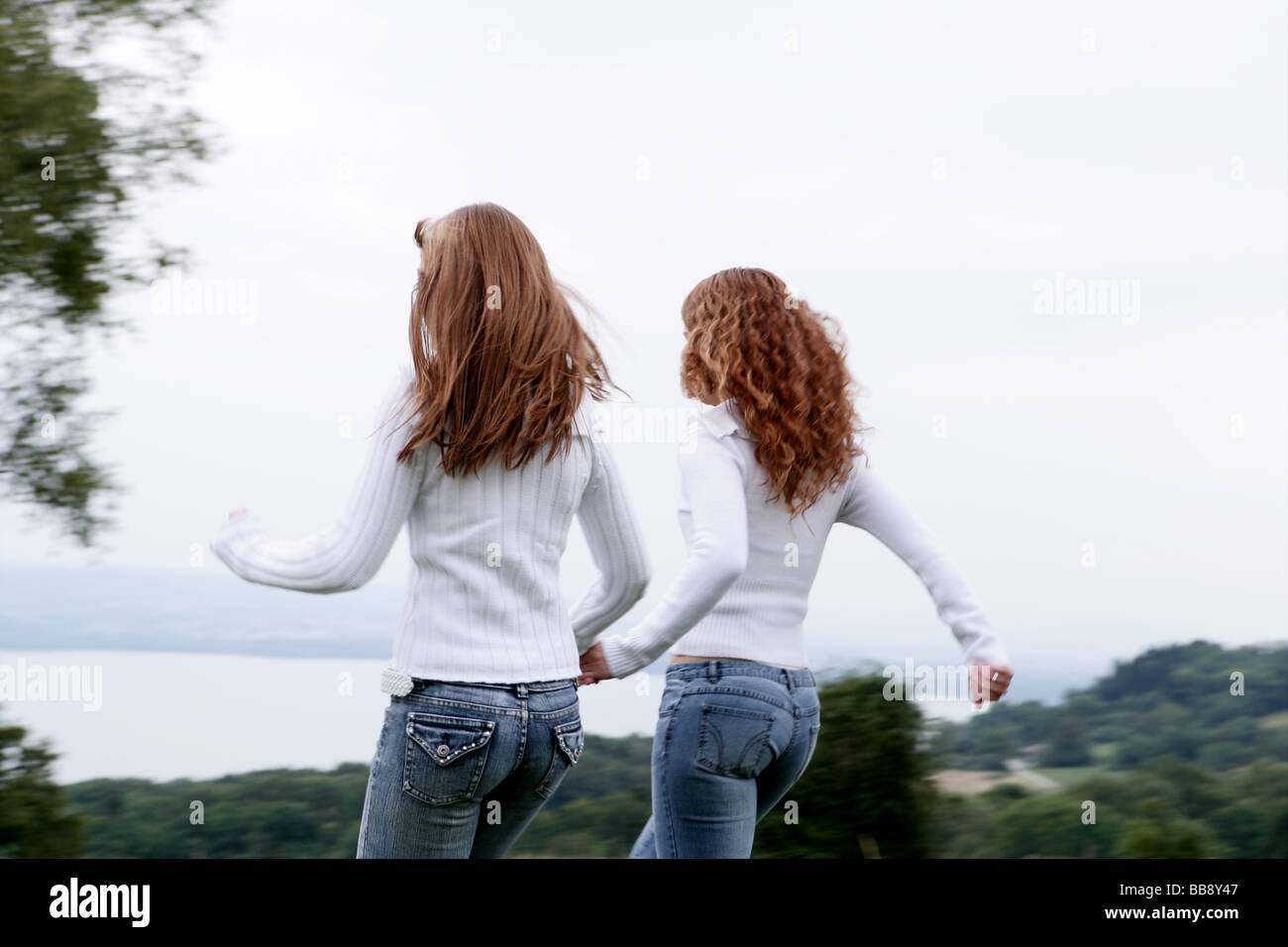 Two teenagers walking on a field with lake view Stock Photo