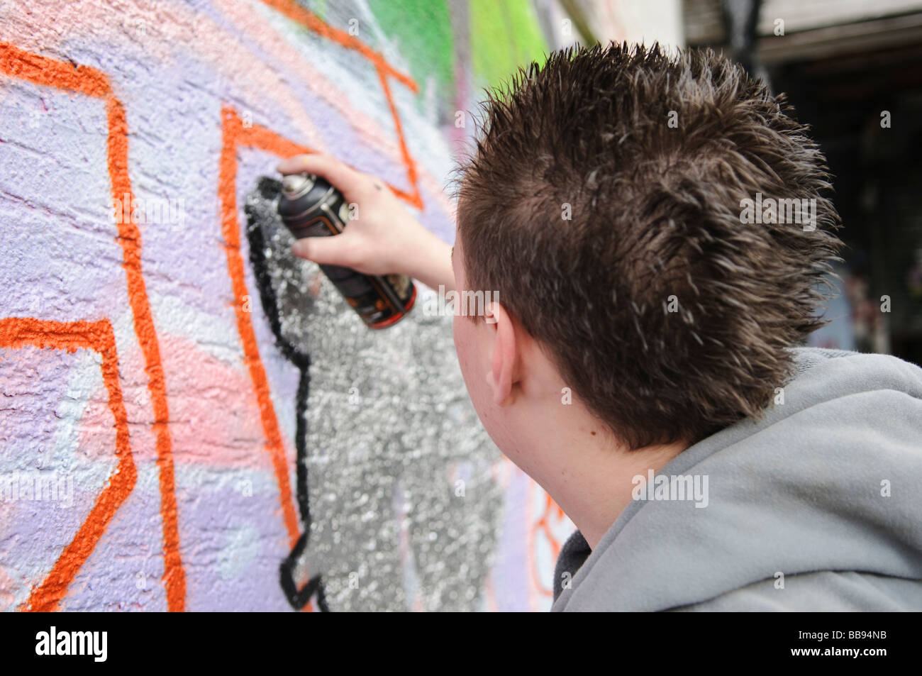 Teenage boy working on a grafitti piece on an exterior wall. - Stock Image