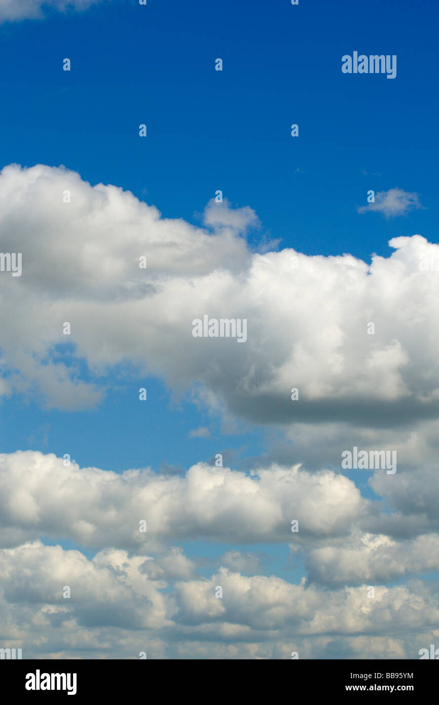 Fluffy clouds across a bright blue sky - Stock Image