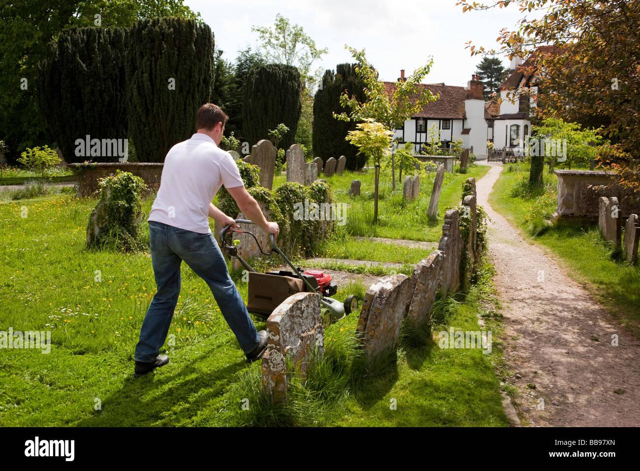 England Berkshire Cookham Holy Trinity Parish Churchyard man mowing graveyard grass with lawn mower - Stock Image