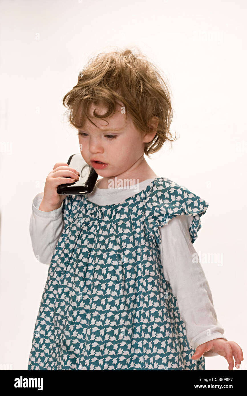 Baby girl pretends to use an iphone - Stock Image