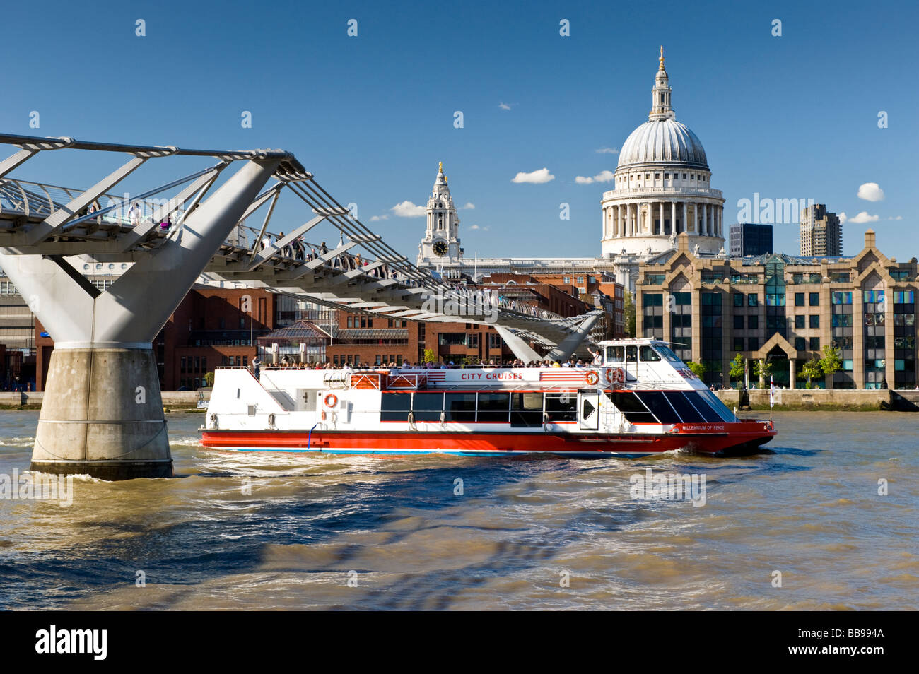 River Thames Tour Boat Passing Beneath the Millennium Bridge with St Pauls Cathedral in Background, London, England, - Stock Image