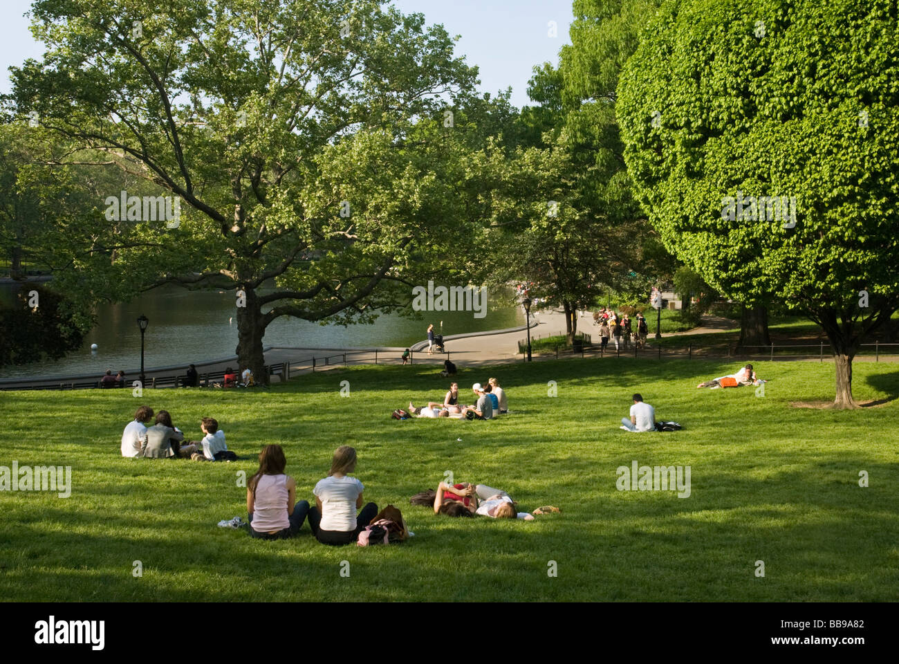 People Relaxing on the lawn by the Conservatory Water in Central Park New York City - Stock Image