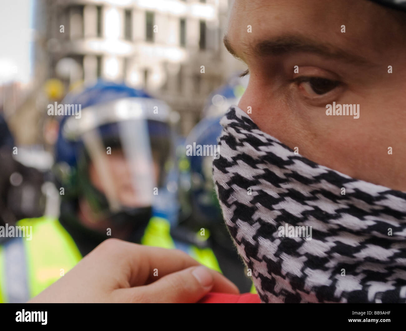 Masked Protestor faces riot police - Stock Image
