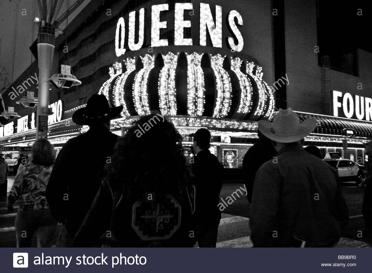 Fremont Street - Las Vegas - location of majority of vintage casinos.  4 Queens Casino lights and passersby - Stock Image