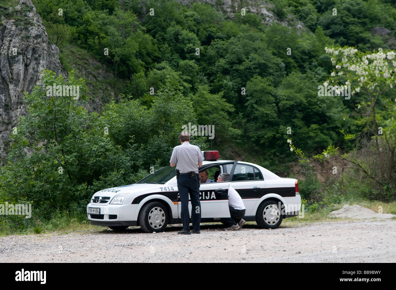 Policemen checking documents of a driver in a police patrol car in Bosnia Herzegovina - Stock Image