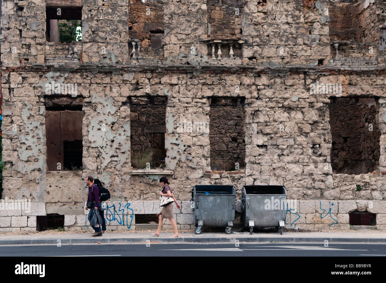 Pedestrians walk past a house showing shrapnel damage from the 1992-95 war in the town of Mostar in Bosnia Herzegovina - Stock Image