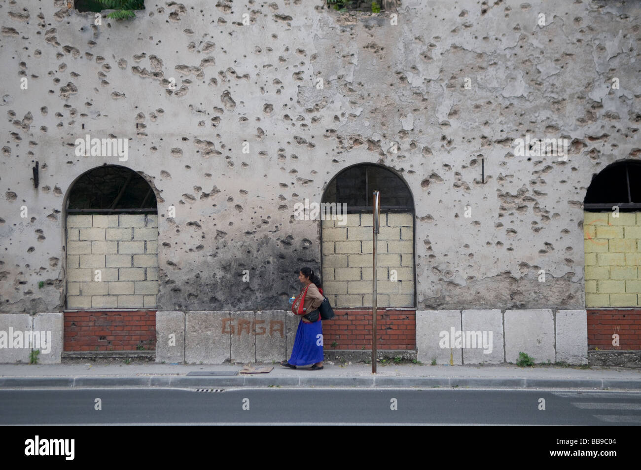 A gypsy woman walk past a house showing shrapnel damage from the 1992-95 war in the town of Mostar in southern Bosnia - Stock Image
