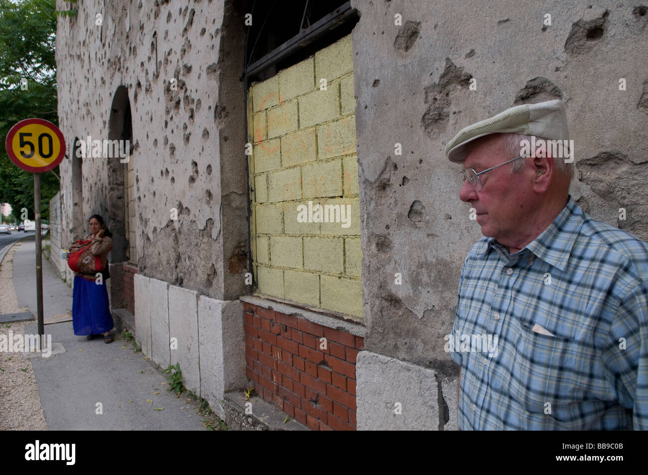 A Bosnian Croat and a Gypsy woman standing by a house showing shrapnel damage from 1992-95 war in Mostar a city - Stock Image
