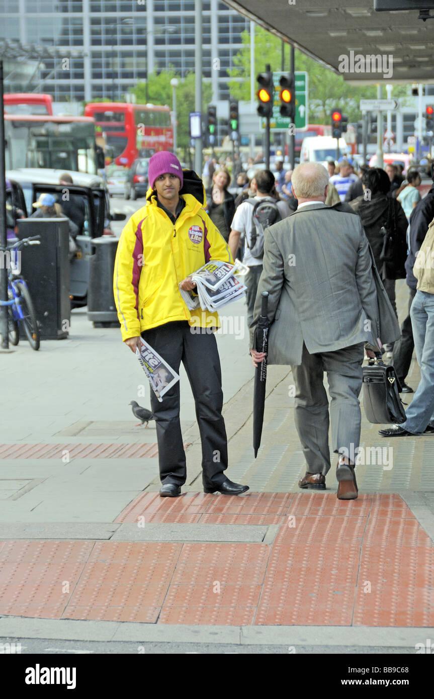 Man distributing London Lite free newspapers in Tottenham Court Road England UK - Stock Image